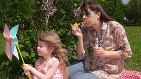 Barnet fostrar och litlledottern på en vårpicknick bredvid en blomstra lila lager videofilmer