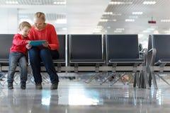 Barnet fostrar och sonen i en flygplatsterminal Royaltyfria Bilder
