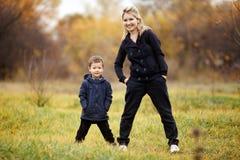 Barnet fostrar och sonen i hösten Forest Park, gul lövverk tillfällig wear Unge som bär det blåa omslaget Ofullständig familj Arkivbilder