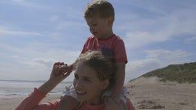 Barnet fostrar och sonen som promenerar stranden arkivfilmer