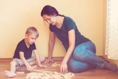 Barnet fostrar och sonen som spelar med inomhus träkvarter Den lyckliga familjen spenderar tid tillsammans hemma Royaltyfri Foto