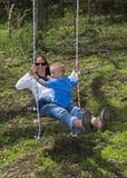 Barnet fostrar och sonen som spelar på en gunga Arkivfoto