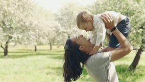 Barnet fostrar och sonen som utomhus spelar Mammavisningförälskelse och affektion till sonen stock video