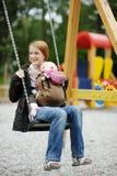 Barnet fostrar på en gunga med behandla som ett barn royaltyfria bilder