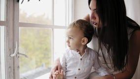 Barnet fostrar sitter med hennes son på fönsterfönsterbrädan som dekoreras med julkransen och ser utanför De är lager videofilmer