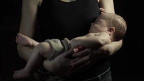 Barnet fostrar vaggar för att sova ett barn i henne armar mörk illustrationlokalvektor stock video