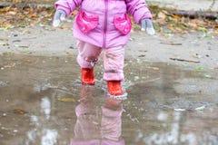 Barnet går i röd stövlar på tips i nedgången Royaltyfria Foton