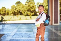 Barnet går till grundskola för barn mellan 5 och 11 år stående av ett lyckligt barn med en portfölj på hans baksida royaltyfri foto