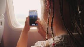 Barnet går tillbaka från semester - gör foto med en smartphone till och med fönstret av nivån Afrikanska flätade trådar är lager videofilmer