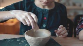 Barnet gör en platta av lera en kurs i krukmakeri lilla flickan gör modeller på en lerastämpel arkivfilmer