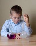 Barnet gör experiment i kemi arkivbild