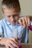 Barnet gör experiment i kemi royaltyfri fotografi