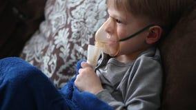 Barnet gör inandning i en special maskering stock video