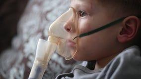 Barnet gör inandning i en special maskering arkivfilmer