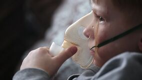Barnet gör inandning i en special maskering lager videofilmer