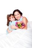 Barnet ger blommor till modern i säng Fotografering för Bildbyråer