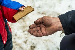 Barnet ger mannen per stycke av rågbröd Royaltyfri Bild