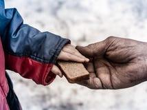 Barnet ger mannen per stycke av rågbröd Arkivbilder