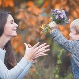 Barnet ger sig till lyckliga moderblommor Nedgången färgar bakgrund Royaltyfria Bilder