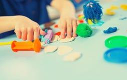 Barnet gjuter från plasticine på tabellen Royaltyfria Bilder