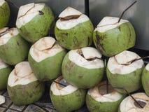 Barnet gör grön kokosnötter för drink Arkivfoto