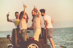 Barnet grupperar att ha gyckel på stranden och att dansa i en konvertibel bil Arkivbilder