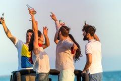 Barnet grupperar att ha gyckel på stranden och att dansa i en konvertibel bil Fotografering för Bildbyråer