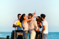 Barnet grupperar att ha gyckel på stranden och att dansa i en konvertibel bil Royaltyfri Fotografi