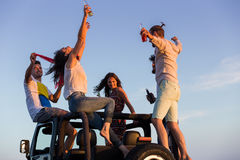 Barnet grupperar att ha gyckel på stranden och att dansa i en konvertibel bil Royaltyfri Foto
