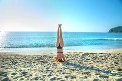 Barnet härlig rödhårig flicka öva yoga på stranden arkivfoto