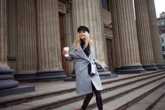 Barnet, höften och den attraktiva blondinen som går runt om staden med kaffe för att gå, ser klockan och skynda sig på affär Arkivbilder