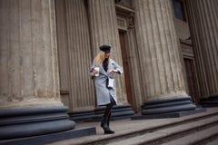 Barnet, höften och den attraktiva blondinen som går runt om staden med kaffe för att gå, ser klockan och skynda sig på affär Fotografering för Bildbyråer
