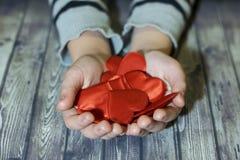 barnet hands hjärta spelrum med lampa Ett barn rymmer en hjärta i hans händer red steg arkivbilder
