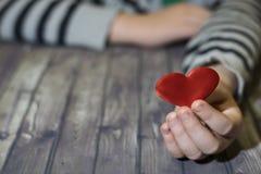 barnet hands hjärta spelrum med lampa Ett barn rymmer en hjärta i hans händer red steg arkivfoto