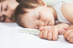 Barnet har en hög temperatur eller en feber, genom att använda en termometer royaltyfria bilder