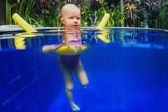 Barnet har en simningkurs på polyfoamnudeln i pöl Arkivbilder