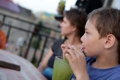 Barnet har fruktsmoothies Arkivbilder