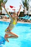 Barnet hoppar i simbassäng Royaltyfria Bilder