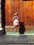 Barnet hoppar nära den gamla dörren arkivfoton