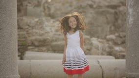 Barnet hoppar på stenen fördärvar av den romerska eran lager videofilmer