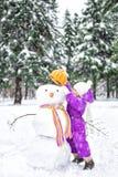 Barnet hugger en snögubbe i snö-täckt parkerar Utomhus- aktiviteter för vinter fotografering för bildbyråer