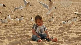 Barnet i en randig t-skjorta kör längs stranden med sand förbi havet stock video