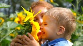 Barnet i hans moders armar som spelar med blomman Royaltyfria Bilder