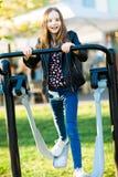 Barnet i jeans ?var att k?ra en utomhus- idrottshallmaskin royaltyfri foto