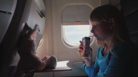 Barnet i kabinen av nivån - dricka fruktsaft från röret, med hennes flygleksak - en hare stock video