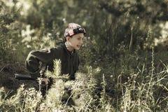Barnet i kamouflage med ett vapen skjuter, laser-etiketten Arkivfoton