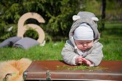 Barnet i parkera ligger på påsen och att spela med gräs Royaltyfri Bild