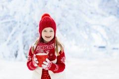 Barnet i röd hatt som dricker varm choklad i snö på jul, semestrar Utomhus- gyckel för vinter Ungar spelar i snöig parkerar på Xm royaltyfri fotografi