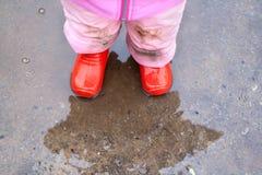 Barnet i röda stövlarkostnader i en höstpöl Royaltyfri Bild