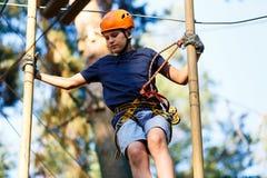 Barnet i skogaffärsföretag parkerar Ungen i orange hjälm och blå t-skjorta klättrar på hög repslinga Vighetexpertis fotografering för bildbyråer